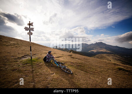 Male backpacker sitting on mountain by bicycle against cloudy sky - Stock Image