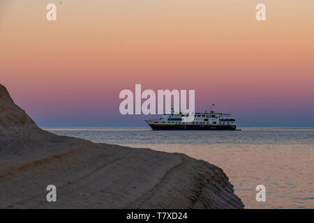The Lindblad National Geographic Venture anchored at sunset off the shore of Isla San Jose, Baja California Sur, Mexico. - Stock Image