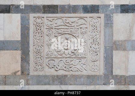 Bas-relief in white marble on the facade of the Carrara cathedral in Tuscany, Italy - Stock Image