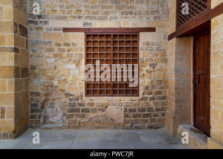 Mamluk era wooden closed window with wooden ornate grid over stone bricks wall, Tekkeyet Al Bustami, Dar El Labana district, Cairo, Egypt - Stock Image