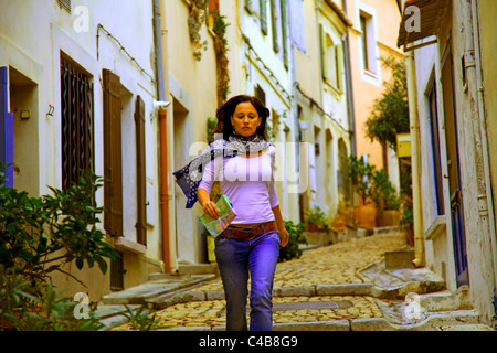 Arles; Bouches du Rhone, France; A young woman walking down the cobbled streets of the Town. MR. - Stock Image