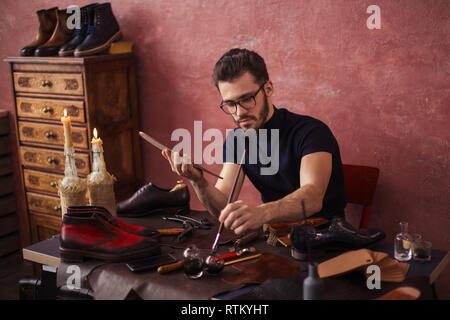 shoe designer concentrated on working with a brush. close up photo. - Stock Image