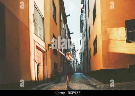 Tourist woman walking in Stockholm enjoying old streets view traveling lifestyle summer vacations in Sweden - Stock Image