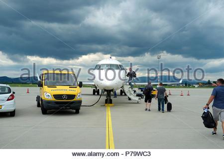 Graz airport - air passengers board their flight under a menacing sky. Graz, in southern Austria. - Stock Image