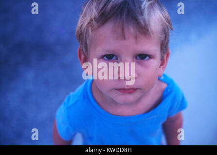 Toddler male boy child looking up at camera wearing blue shirt - Stock Image