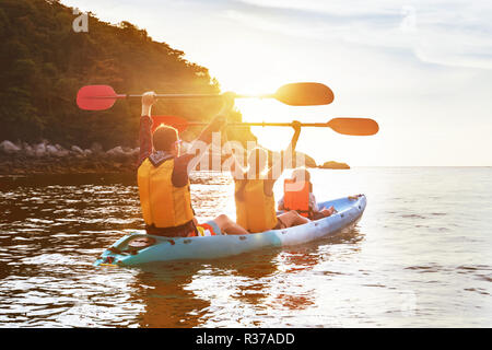 Happy family is walking at sunset sea by kayak or canoe. Active tourism concept - Stock Image