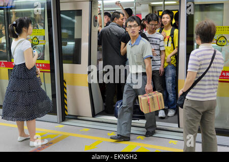 Passengers get off a metro train in Guangzhou, China. Screen doors can clearly be seen between the platform train - Stock Image