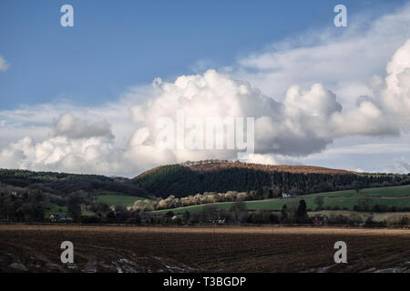 A huge cumulus cloud hangs over hills above the tiny hamlet of Stapleton, near Presteigne, Powys, UK, - Stock Image