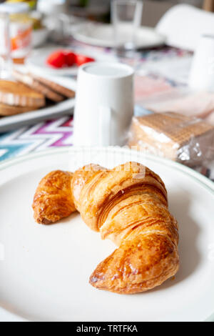 closeup of a croissant in a plate on a table set for breakfast, next to a white ceramic pot with milk and some trays with toasts and cold cuts - Stock Image