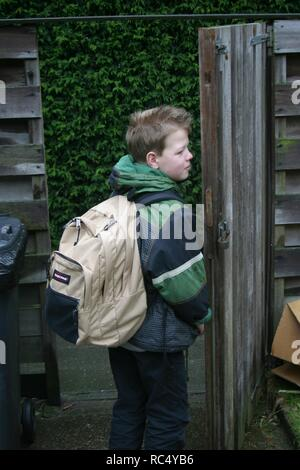 Elementary boy with back-pack standing at the gate, waiting for school drop-off. - Stock Image