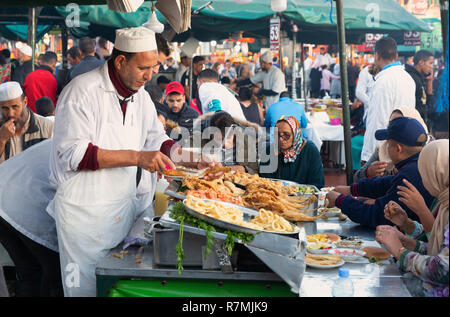 Marrakech street food - tourists and locals eating in the evening at a food stall in Djemaa el Fna square, Marrakech medina, Morocco Africa - Stock Image