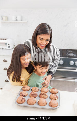 Mother and children baking chocolate muffins in kitchen - Stock Image