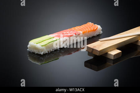sushi on black background with chopsticks. wooden press form for making sushi - Stock Image