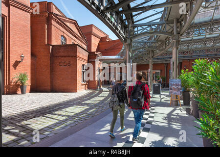 Shopping centre center, rear view of young people walking towards the entrance to a shopping mall - the Stary Browar - in the city of Poznan, Poland. - Stock Image