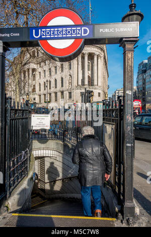 Public subway entrance and man descending steps to Charing Cross Underground tube station, located on Trafalgar - Stock Image