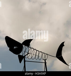 A metal sculpture in the form of a shark skeleton against a cloudy sky - Stock Image