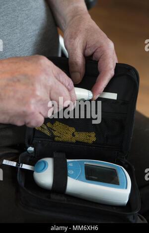 Senior man using pen-like lancing device to prick finger - Stock Image