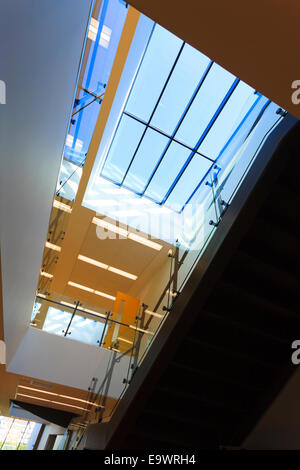 Looking up into atrium in corridor of modern building - Stock Image