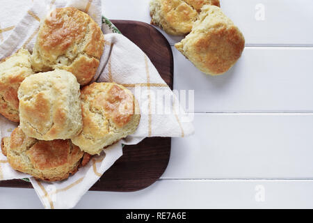 Fresh buttermilk southern biscuits or scones over a white table shot from above. Top view. - Stock Image