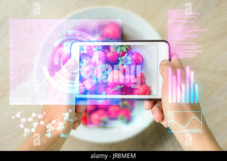 Woman holding a smart device uses reality augmentation to examine a pile of strawberries - Stock Image
