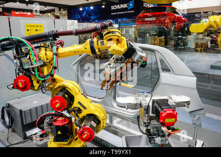 31.03.2019, Hannover, Lower Saxony, Germany - Hanover Fair, industrial robots welding and transporting cars at the Fanuc booth. 00X190331D013CAROEX.JP - Stock Image