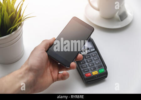 nfc contactless payments - hand holding phone above payment terminal - Stock Image
