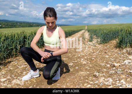 woman jogger checking her smart watch - Stock Image