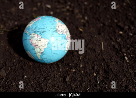 Color globe of planet earth with a dirt mud background - Stock Image