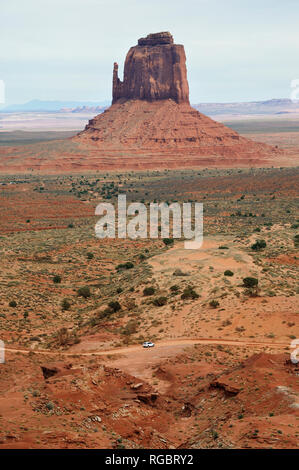 White SUV driving on a dirt road in Monument Valley, Arizona, with the Right Mitten in the background. - Stock Image