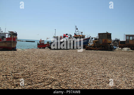Hastings, UK -July 14 2018: Fishing boats docked on the pebbles beach of the port of Hastings on a hot summers day as the temperatures sore to above 27 degrees on 14 July 2018.  Hastings on the south coast of England is 53 miles south-east of London and is 8 miles from where the  Battle of Hastings took place in October 1066. Credit: david mbiyu/Alamy Live News - Stock Image