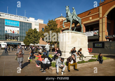 People sitting around the Lady Godiva statue on Broadgate in Coventry city centre UK - Stock Image