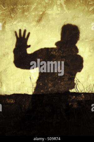 Stop! No more! Man casting a shadow on a wall expressing, Stop!, No more! - Stock Image