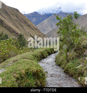 Ancient irrigation channels carrying glacial water through farmland in the Urubamba Valley. Cusco, Peru - Stock Image