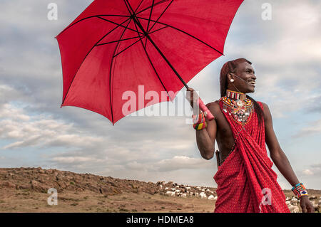 A Maasai Warrior smiles happily wearing traditional beaded tribal jewelry.and holding a red umbrella. Kenya, Africa. - Stock Image