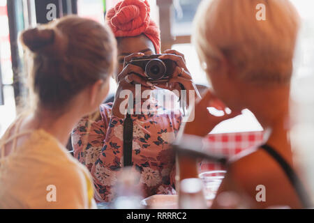 Young woman photographing friends with camera in restaurant - Stock Image