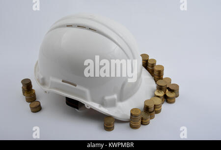 Helmet with coins isolated on white background - Stock Image