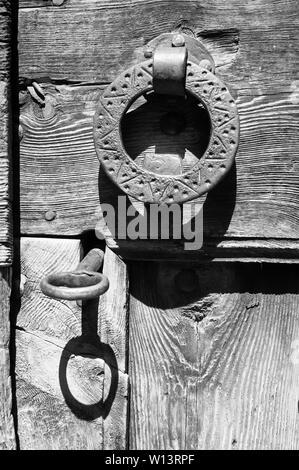 Antique rustic metal key in door lock and metal knocker from an old wood door in Gistaín (Chistau valley, Sobrarbe, Huesca, Aragón,Spain). B&W version - Stock Image