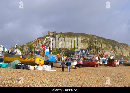 Couple strolling past Hastings fishing boats on the Old Town Stade beach on a stormy day in winter, East Sussex, UK - Stock Image