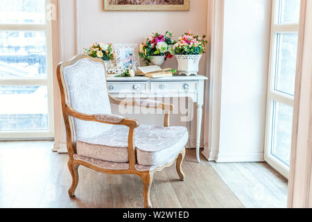 Beautiful luxury classic white bright clean interior bedroom in baroque style with large window, armchair and flower composition - Stock Image