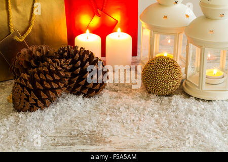 Wooden Christmas background with candles, pine cones, shopping bags and baubles. - Stock Image