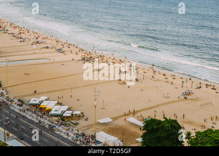 Aerial top view of People relaxing on beach and at kiosks along Copacabana Beach in Rio de Janeiro, Brazil. - Stock Image