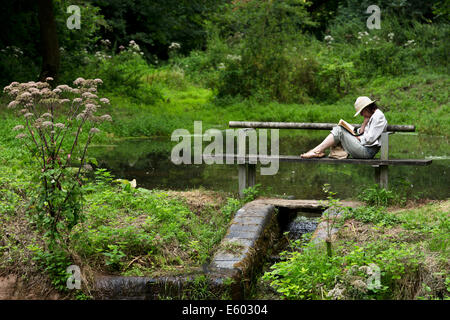 An interesting read. Mature woman reading a book whilst sitting on a bench next to a lake in Hestercombe Gardens. - Stock Image