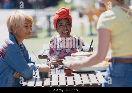Young women friends enjoying lunch at sunny sidewalk cafe - Stock Image