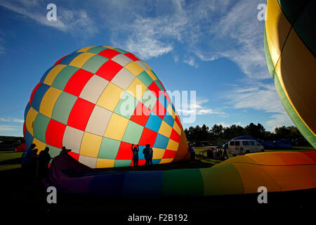 Silhouettes against an inflating hot air balloon at the 30th annual Atlantic International Balloon Fiesta, Sussex, - Stock Image