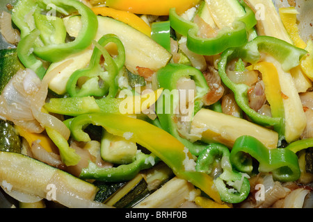 Courgettes onions yellow and green peppers frying in olive oil - Stock Image