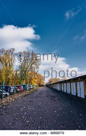 Row of garage doors and parked cars along a footpath with fallen leaves in Poznan, Poland - Stock Image