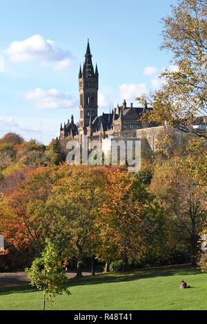 A student relaxes on the grass in Kelvingrove Park in Autumn below Glasgow University, Scotland, UK, Europe - Stock Image