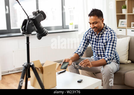 male blogger with smartphone, wire and parcel box - Stock Image