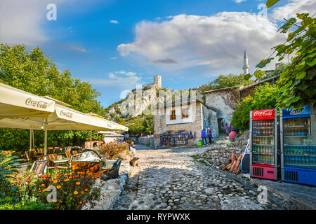 A dog sits outside the outdoor seating for a cafe in the medieval city of Pocitelj Capljina under the Kula tower in Bosnia and Herzegovina - Stock Image