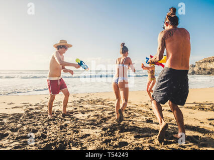 Group of people young caucasian men and women play with water gun at the beach during friends vacation together in outdoor in a sunny day of holiday - - Stock Image